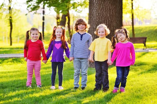 Un groupe de petits enfants souriants tenant par la main sur un fond d'herbe, un arbre et un parc. Photo Premium
