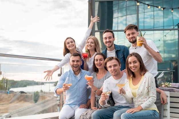 Groupe posant lors d'une soirée sur la terrasse Photo gratuit