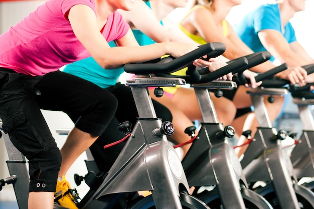 Groupe de quatre personnes tournant dans la salle de sport, exerçant leurs jambes en cardio-training Photo Premium