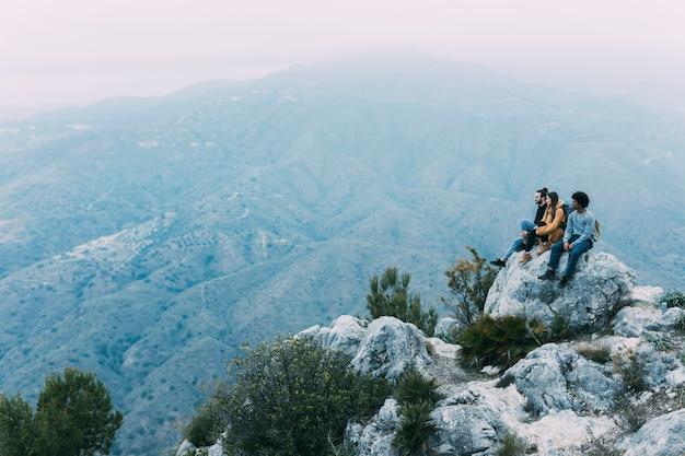 Groupe de randonneurs assis sur un rocher Photo gratuit
