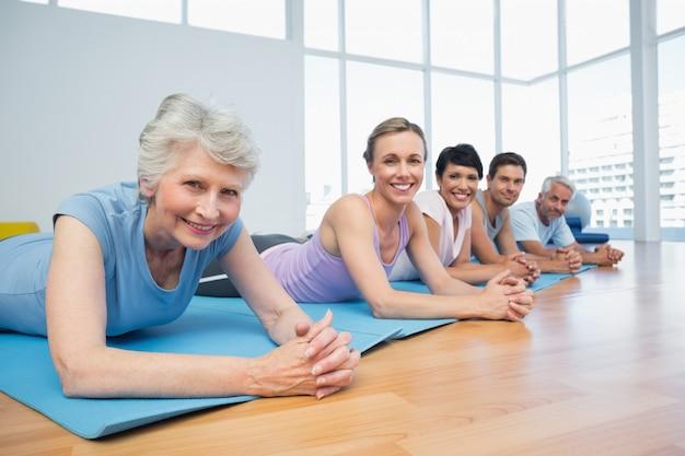 Groupe de remise en forme allongé dans une classe de yoga Photo Premium