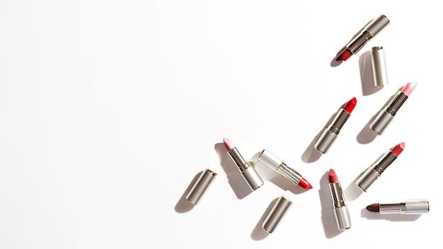 Groupe de rouges à lèvres métalliques sur fond blanc Photo gratuit