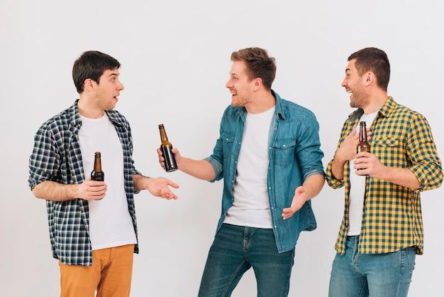 Groupe de sourire trois amis masculins appréciant la bière Photo gratuit