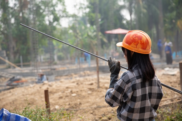 Un groupe de tiges d'acier serrées par chaîne et soulevées sur le chantier Photo gratuit