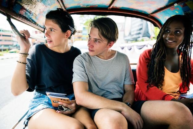 Groupe de touristes apprécient la conduite de taxi indigène de tuk tuk Photo Premium