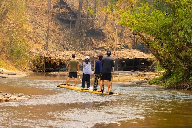 Groupe de touristes visitant et assis sur le radeau de bambou flottant rafting et ramer sur les rapides. Photo Premium