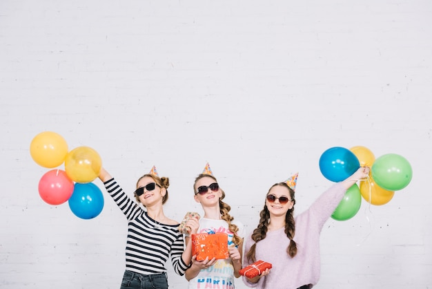Groupe de trois amies profitant de la fête avec des cadeaux et des ballons Photo gratuit
