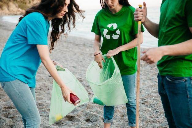 Groupe de trois bénévoles collecte des ordures à la plage Photo gratuit
