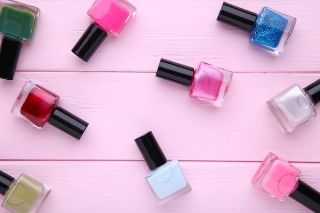 Groupe de vernis à ongles brillants sur fond rose Photo Premium