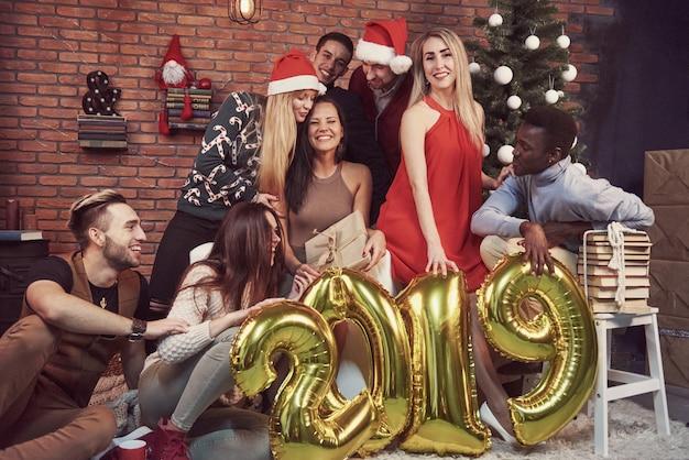 Un Groupe De Vieux Amis Joyeux A Fait Un Cadeau à Une Fille. La Nouvelle Année 2019 Arrive. Célébrez Le Nouvel An Dans Une Atmosphère Chaleureuse Photo Premium