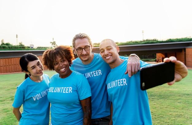 Groupe de volontaires divers réunissant selfie Photo gratuit