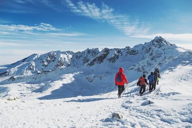 Groupe de voyageurs vont à la grande randonnée de montagne en hiver. paysages Photo Premium