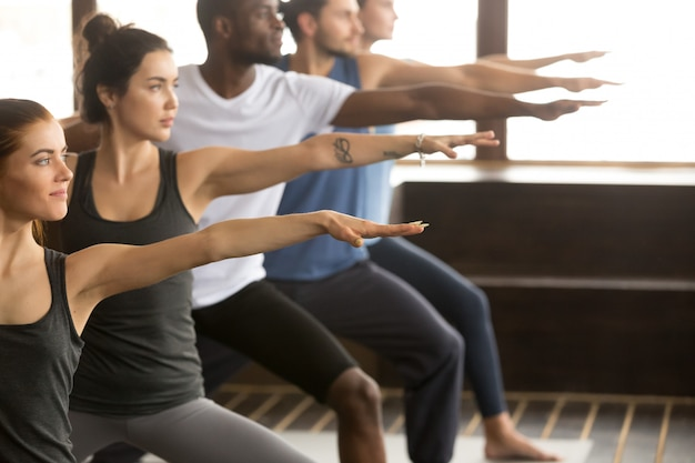Groupe de yogi dans warrior two pose Photo gratuit