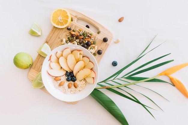 Gruau sain et fruits secs sur une planche à découper avec fleur Photo gratuit