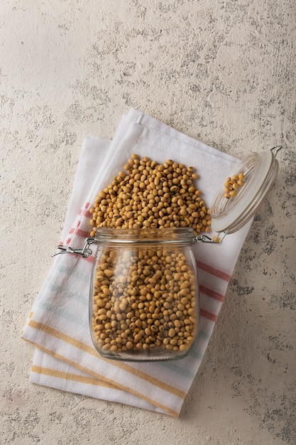 Gruau De Soja Entier Produit Stable Sur Le Plateau. Aliment Végétarien, Le Soja Est Une Source De Protéines. Grains De Soja Dans Un Bocal En Verre Sur Béton Gris. Photo Premium