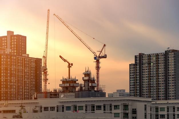 Grue et chantier de construction travaillant sur un complexe au coucher du soleil, développement du concept de ville Photo Premium