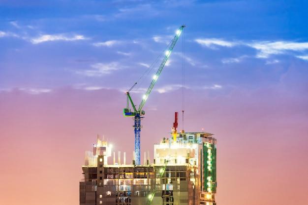 Une grue industrielle lourde en activité sur le chantier de construction d'une nouvelle infrastructure complexe Photo Premium