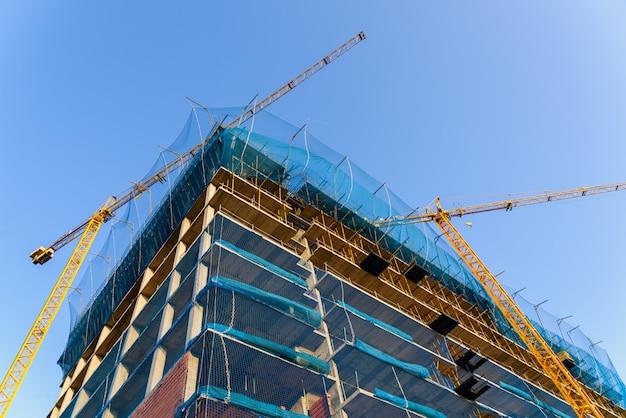 Grue jaune sur un chantier de construction pour soulever de gros poids de matériaux de construction et permettre aux maçons de mener à bien leurs travaux. Photo Premium