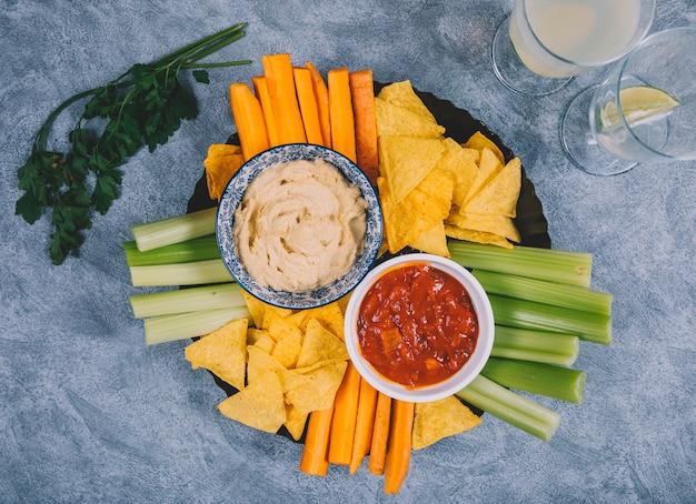 Guacamole et sauce salsa dans un bol avec la carotte; tige de céleri; jus; chips de coriandre et tortilla sur fond de béton Photo gratuit