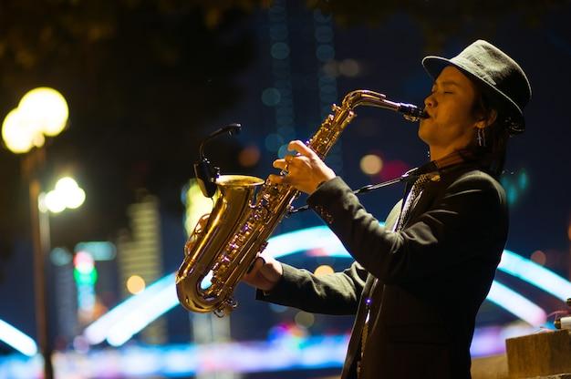 Guangzhou, chine - 15 mars 2016: homme jouant du saxophone dans la rue dans la soirée Photo Premium