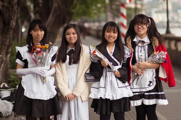 Guangzhou, chine - 15 mars 2016: quatre chinoises souriantes, jolies filles étudiantes à l'école, s'habillent avec des fleurs Photo Premium