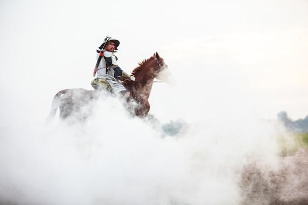 Guerrier mâle en armure à cheval dans le brouillard blanc Photo Premium