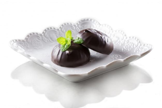 Guimauve au chocolat et une feuille de menthe isolée sur fond blanc Photo Premium