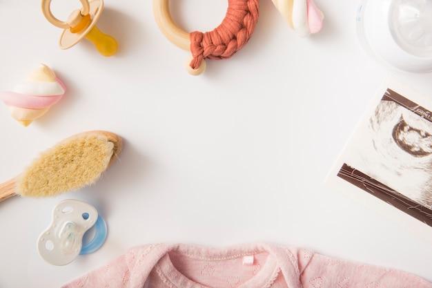 Guimauve; body bébé rose; brosse; sucette; bouteille de lait et jouet sur fond blanc Photo gratuit