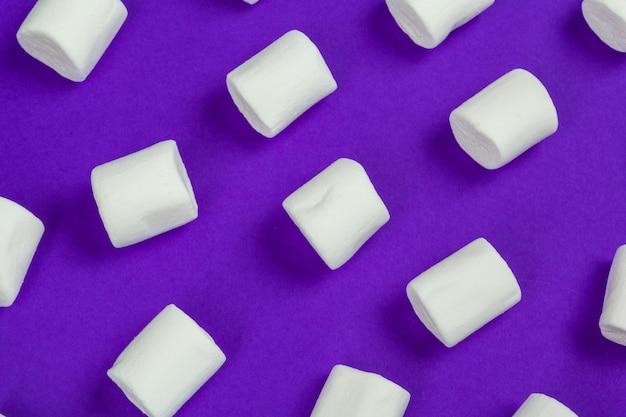 Guimauve disposée sur du papier violet. Photo Premium