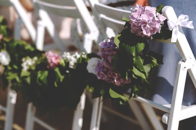 Guirlande de feuilles et hortensias violettes sur les chaises. Photo gratuit