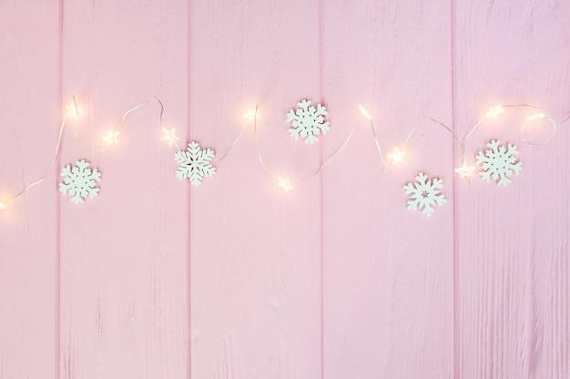 Guirlande De Lumières De Noël Avec Frontière De Flocons De Neige Sur Bois Rose Photo Premium