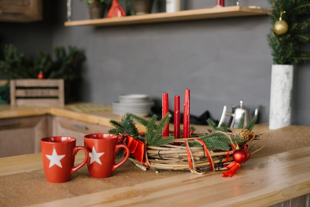 Une Guirlande De Noël Avec Des Bougies Rouges Sur La Table En Bois Et Deux Tasses Rouges Dans La Cuisine, Photo Premium