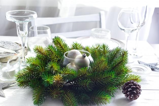 Guirlande de noël avec des jouets sur la table avec cadre de table de noël argenté Photo Premium