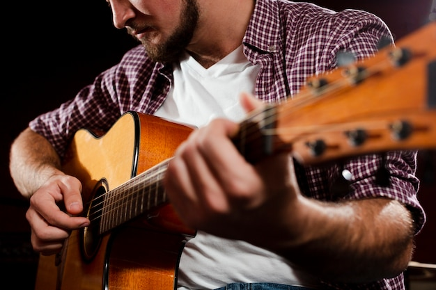 Guitare Acoustique Floue Et Gars Jouant Au Gros Plan Photo gratuit