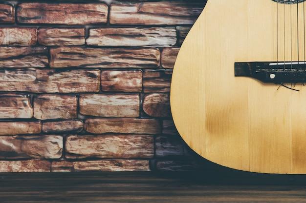 Guitare acoustique se dresse sur un fond de mur de brique. Photo Premium