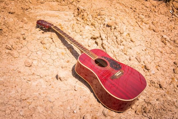Guitare acoustique se trouvant sur une terre déserte Photo Premium