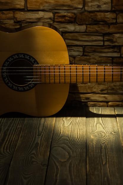 La guitare acoustique se trouve sur le fond d'un mur de briques. Photo Premium