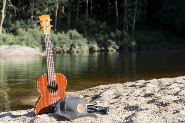 Guitare avec capuchon et lunettes de soleil sur le rivage près de l'eau Photo gratuit