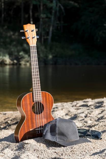 Guitare avec capuchon et lunettes de soleil sur le rivage près de la surface de l'eau Photo gratuit