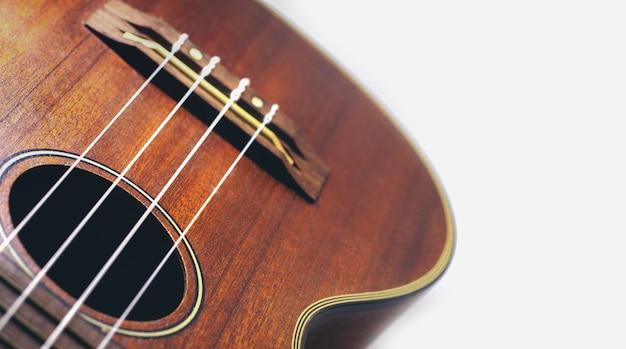 Guitare ukulélé brun sur le fond blanc vacances relax temps de pause avec la musique Photo Premium