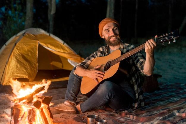 Guitariste campant la nuit près d'un feu de camp Photo gratuit