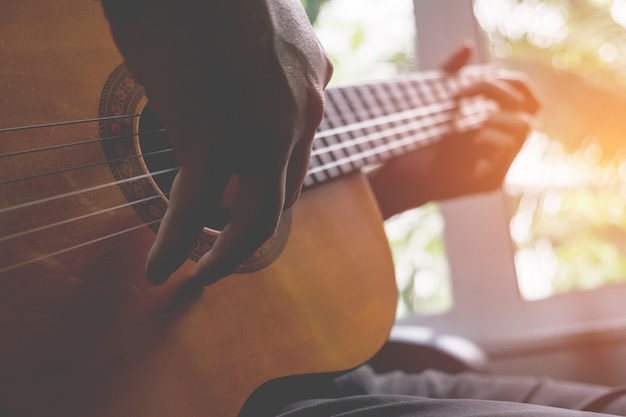 Le guitariste de la guitare acoustique joue. instrument de musique avec les mains des interprètes. Photo gratuit