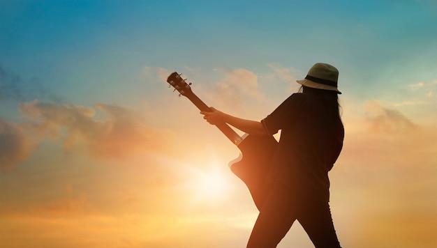 Guitariste Jouant De La Guitare Acoustique Au Coucher Du Soleil Photo Premium
