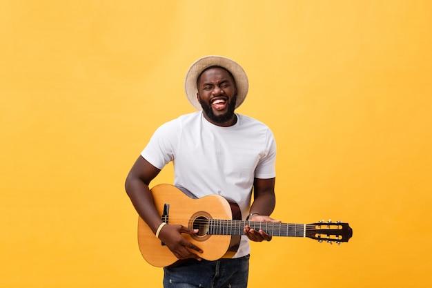 Guitariste de style afro-américain jouant de la guitare acoustique isolée sur fond jaune. Photo Premium