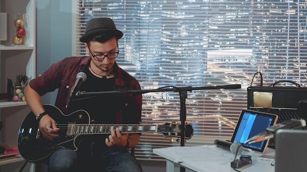 Guitariste De Talent En Chapeau Et Vêtements Décontractés à La Mode, Jouer De La Guitare Et Chanter En Studio D'enregistrement à Domicile Photo Premium