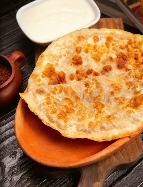 Gutab caucasien traditionnel, kutab, gozleme avec sumakh et yaourt dans une assiette en bois. Photo gratuit
