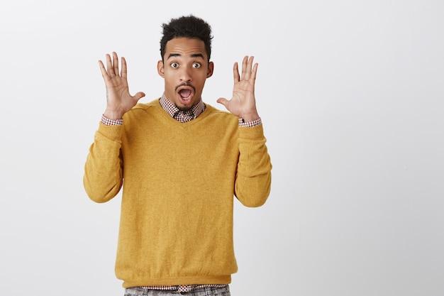 Guy Avait Peur D'une Détonation Ininterrompue. Portrait D'afro-américain Drôle Attrayant Avec Coiffure Afro Soulevant Les Paumes Près Du Visage, Criant De Surprise Et D'étonnement, La Mâchoire Tombante Et Haletant Photo gratuit