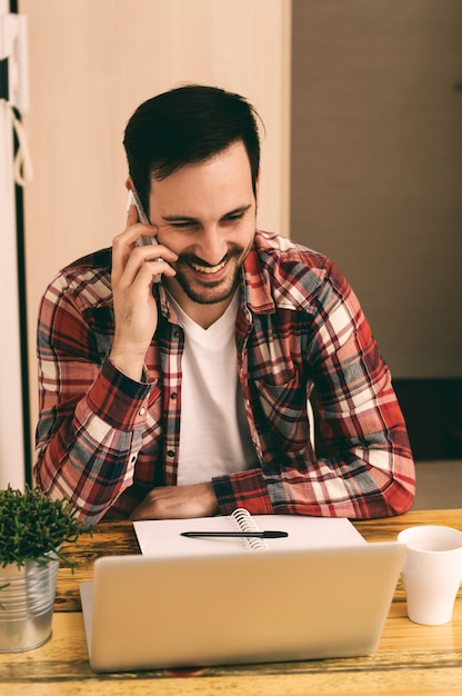 Guy en chemise à l'aide de téléphone et de boire du café Photo Premium