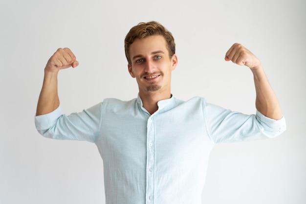 Guy ciblé en chemise blanche décontractée montrant le geste de force. Photo gratuit