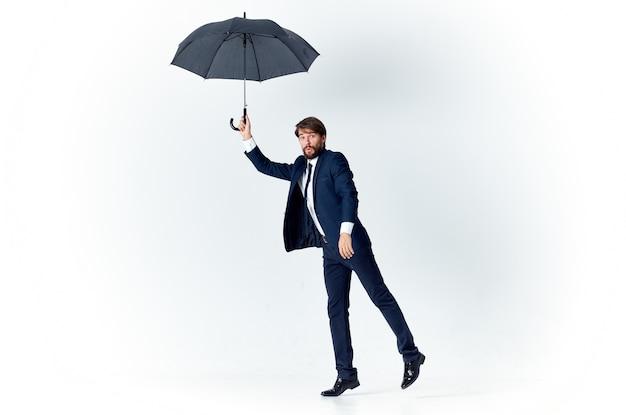 Guy En Costume Avec Un Parapluie à La Main Sur Un Fond Clair Par Temps Venteux Photo Premium